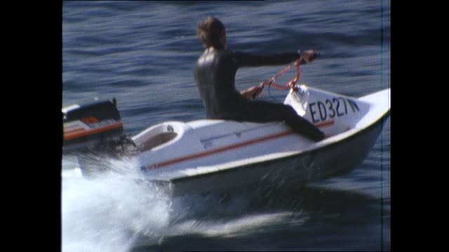 vs ken white rides java scrambler jet ski style water bike boat on sydney harbour / reporter jenny harvey drives jet ski with white as passenger /... - acquascooter video stock e b–roll