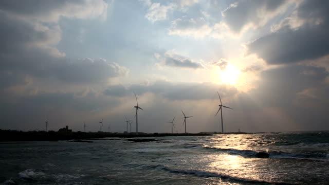 w of wind turbine alongside Sinchang coast road at sunset