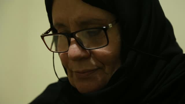 waad al-kateab reflects on 10 years of war in syria; lebanon: beirut: int hajjeh fadwa looking at family photos - war and conflict video stock e b–roll
