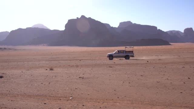 vídeos y material grabado en eventos de stock de wadi rum - a local car crossing fast, in sandstone desert landscape - pared de roca