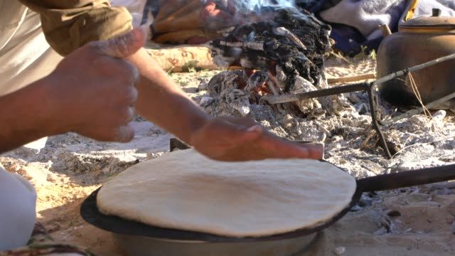 vídeos y material grabado en eventos de stock de wadi rum desert, jordan; march 22, 2019; zalabia bedouin preparing traditional arabic bread in wadi rum desert, jordan. abud is a dense, unleavened... - leña