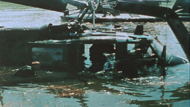 wading soldiers recovering equipment and belted ammunition from helicopter downed in ba lai river / vietnam - wading stock videos & royalty-free footage