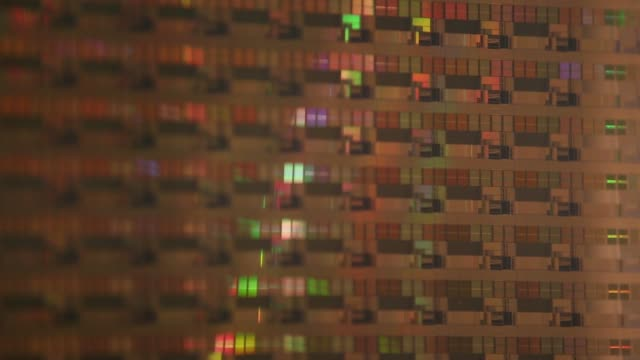 vídeos de stock e filmes b-roll de a wafer of silicon used to make microprocessor chips stands on display close up pull focus into a wafer of silicon microprocessor chips on display... - silício