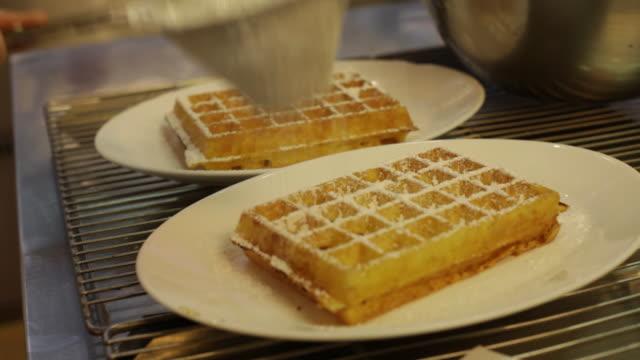 vídeos y material grabado en eventos de stock de waffles with icing sugar being sprinkled on tip in antwerp, belgium - waffles
