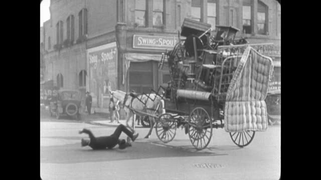 stockvideo's en b-roll-footage met 1922 wagon driver (buster keaton) accidentally knocks out traffic cop - paardenkar