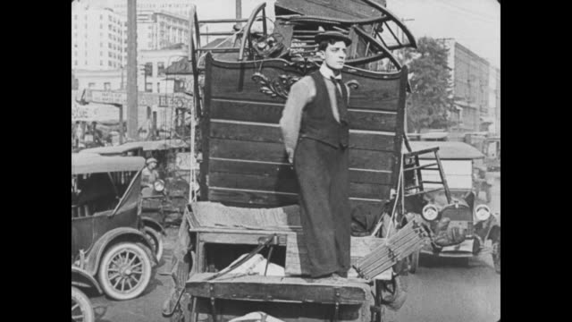 1922 Wagon driver (Buster Keaton) tries to take nap on busy street