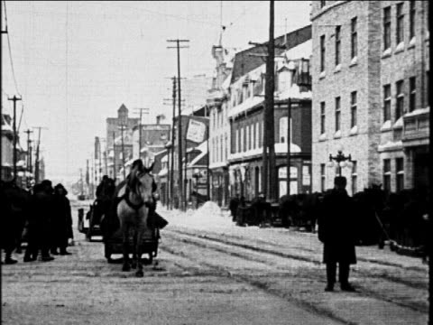 B/W 1927 wagon pulling sled on city street / Canada / industrial
