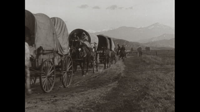 WS wagon train moving on road with mountains in background / United States