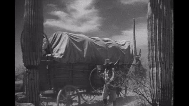wagon train rides through desert, passes by sleeping man - selvaggio west video stock e b–roll