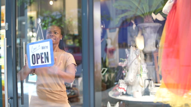 waist up african woman placing open sign on store window - store sign stock videos & royalty-free footage