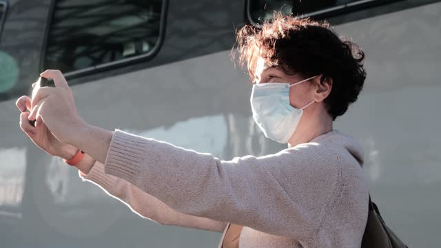 vidéos et rushes de verticale de taille vers le haut du masque de visage de femme de sourire qui faisant le selfie utilisant son téléphone intelligent en attendant le train sur la plate-forme de gare - transports publics