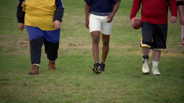 Waist-down panning view of amateur football players walking towards camera