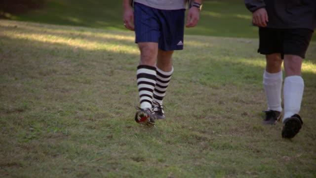 vídeos y material grabado en eventos de stock de waist-down view of soccer players walking toward camera - de lado a lado