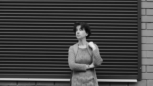 stockvideo's en b-roll-footage met waist-up portrait of mature woman standing against the striped wall - one mature woman only