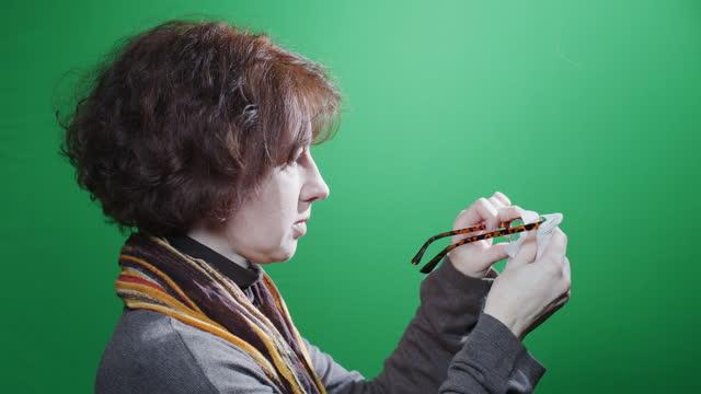 vidéos et rushes de verticale de taille-vers le haut de femme mûr essuyant ses lunettes au-dessus du fond vert de clé de chroma - profil