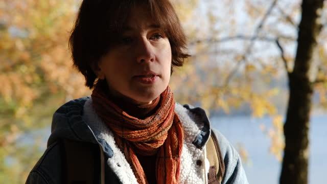 stockvideo's en b-roll-footage met waist-up portrait of woman walking on lakeshore in sunny autumn nature park - sunny