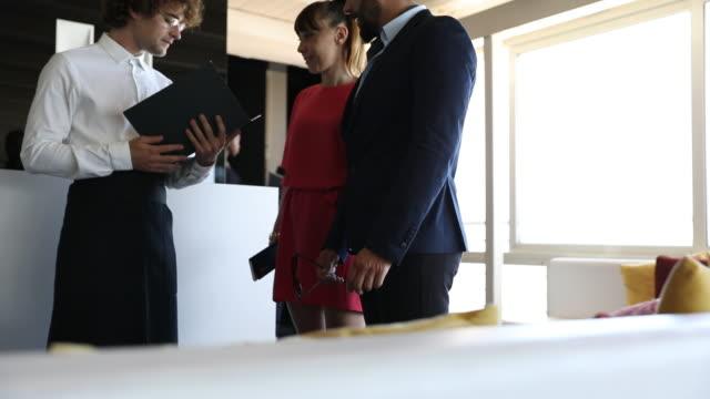 vidéos et rushes de le personnel d'attente d'un restaurant de luxe accueille les clients d'affaires - entrée
