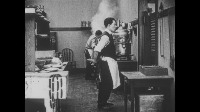 1918 waiter (buster keaton) barks food orders at chef (fatty arbuckle) who deftly throws order for waiter to catch - buster keaton stock videos and b-roll footage