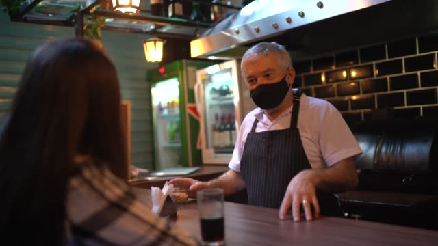 vídeos de stock e filmes b-roll de a waiter behind the counter taking to client's in a restaurant - using face mask - bar