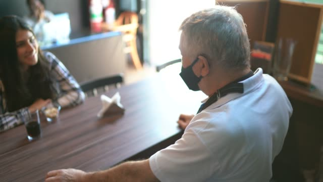a waiter behind the counter taking to client's in a restaurant - using face mask - serving staff stock videos & royalty-free footage