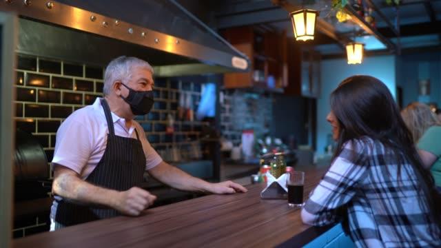 vídeos de stock, filmes e b-roll de um garçom atrás do balcão levando para o cliente em um restaurante - usando máscara facial - proteção