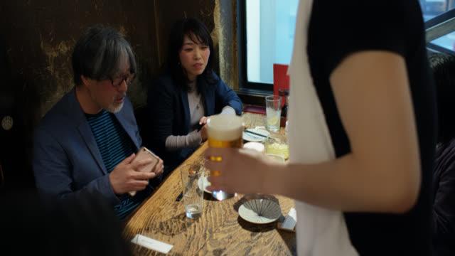 東京のレストランでお客さんにビールを持ってくるウェイター - サービス点の映像素材/bロール