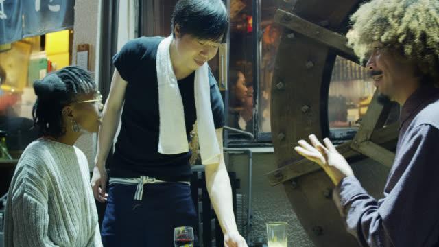 東京のバーの外のテーブルでカップルに食べ物を持って来るウェイター - ウェイター点の映像素材/bロール