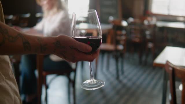 kellner bringt rotwein zum kunden im argentinischen restaurant - italienischer abstammung stock-videos und b-roll-filmmaterial