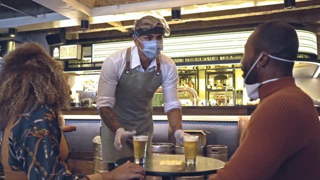 vídeos de stock, filmes e b-roll de garçom traz cerveja para a mesa dos clientes - drink