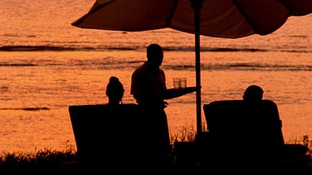 vídeos de stock, filmes e b-roll de orange silhouette waiter brings drinks to couple sitting under umbrella with water in background / indonesia - chapéu de sol