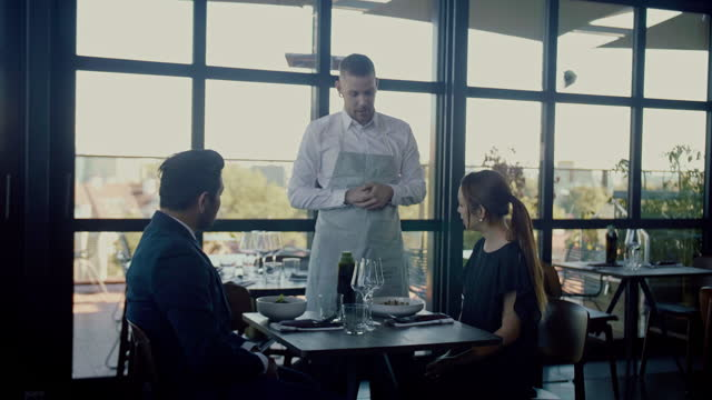 ウェイターは素敵なレストランで食べ物をテーブルに持って来ます - 高級料理点の映像素材/bロール