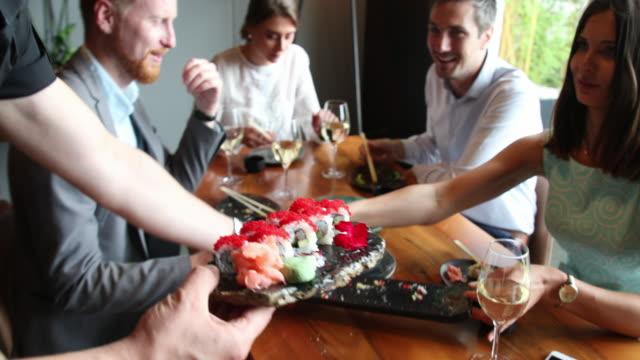 waiter brings sushi to dining table - sushi video stock e b–roll