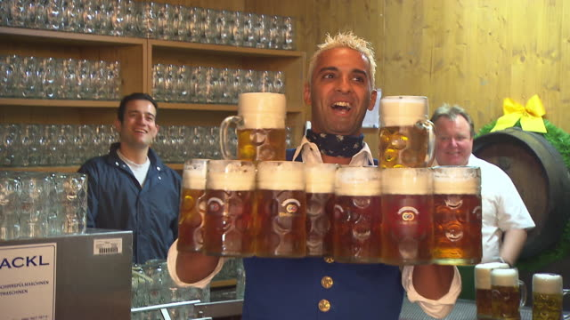waiter carries beer mugs