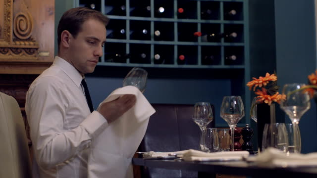 MS Waiter cleaning wine glass in restaurant