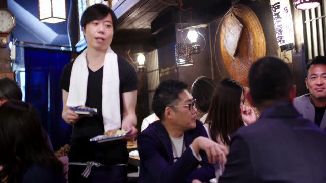 waiter delivering food to a table at a japanese izakaya - food and drink establishment stock videos & royalty-free footage