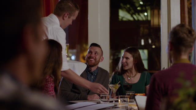 waiter delivers cocktails and beer to dining party at upscale restaurant - gourmet stock videos & royalty-free footage