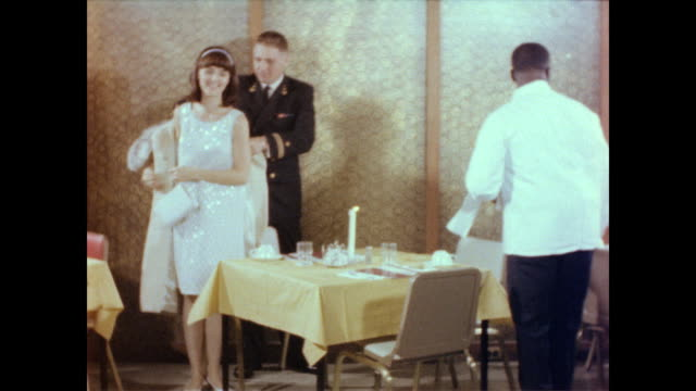 / waiter escorts woman and her military date to table / man helps date off with her coat and holds chair out for her / man stands to introduce his... - マナー点の映像素材/bロール