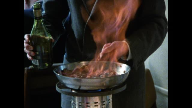 vidéos et rushes de waiter flambés meal at table before serving; 1986 - alcool
