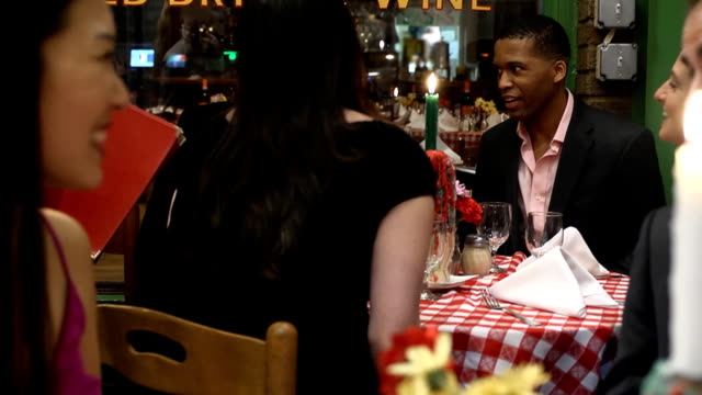 waiter giving menus to friends at table - evening meal stock videos and b-roll footage