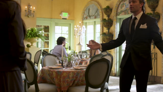 waiter greeting women and taking them to table. - grandangolo tecnica fotografica video stock e b–roll