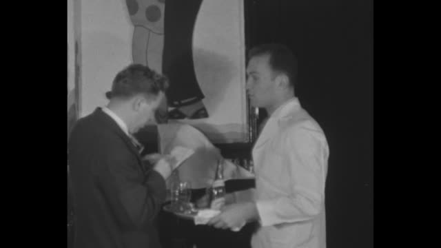 waiter holding tray with bottle and glass on it talks to man who writes down what waiter says another man walks by and says something to waiter... - tablett oder küchenblech stock-videos und b-roll-filmmaterial