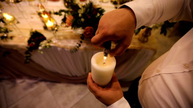 waiter lights a candle decoration for a wedding evening - banquet hall stock videos & royalty-free footage
