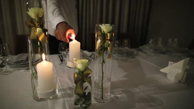 vidéos et rushes de serveur allume la bougie sur une table - kérosène