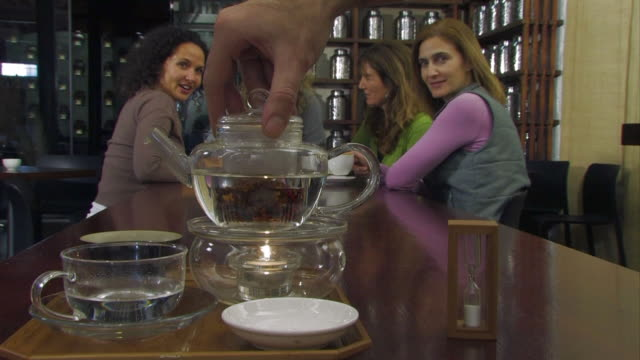 ms waiter mixing tea leaf canister into glass tea pot / cape town, western cape, south africa - tea pot stock videos and b-roll footage