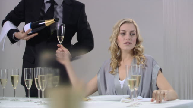 Waiter pouring champagne for woman who raises glass