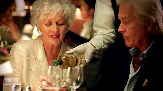 ms waiter pouring wine for senior couple in upscale restaurant / they toast - 年配のカップル点の映像素材/bロール