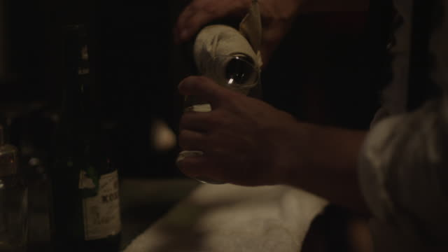 a waiter pours champagne into a glass from a bottle wrapped in a towel. - wrapped in a towel stock videos & royalty-free footage