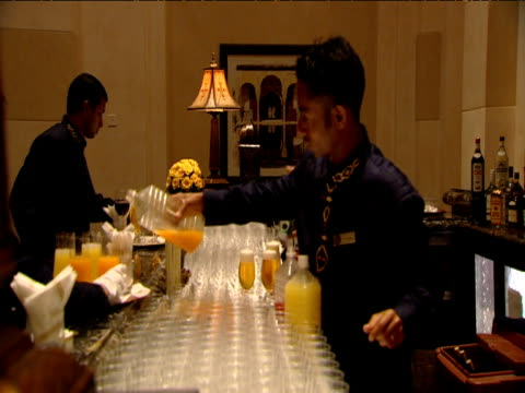 waiter pours juice into glasses at function in luxury hotel others work busily around him dubai - ワインバー点の映像素材/bロール