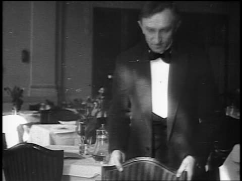 b/w 1916 waiter pulling out chair for woman who sits down at table in posh restaurant / newsreel - newsreel stock videos and b-roll footage