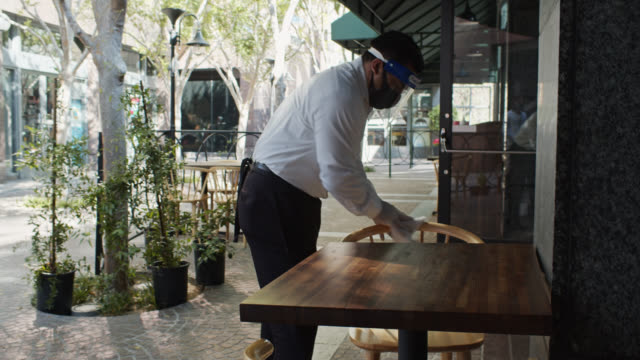 waiter sanitizing table and chairs during covid-19 pandemic - patio stock videos & royalty-free footage